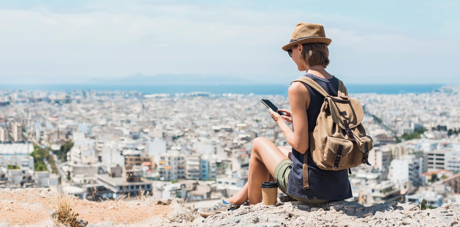 Young woman using smartphone during vacations. Girl holding mobile phone with a big city at background. Travel, lifestyle, tourist royalty free stock image