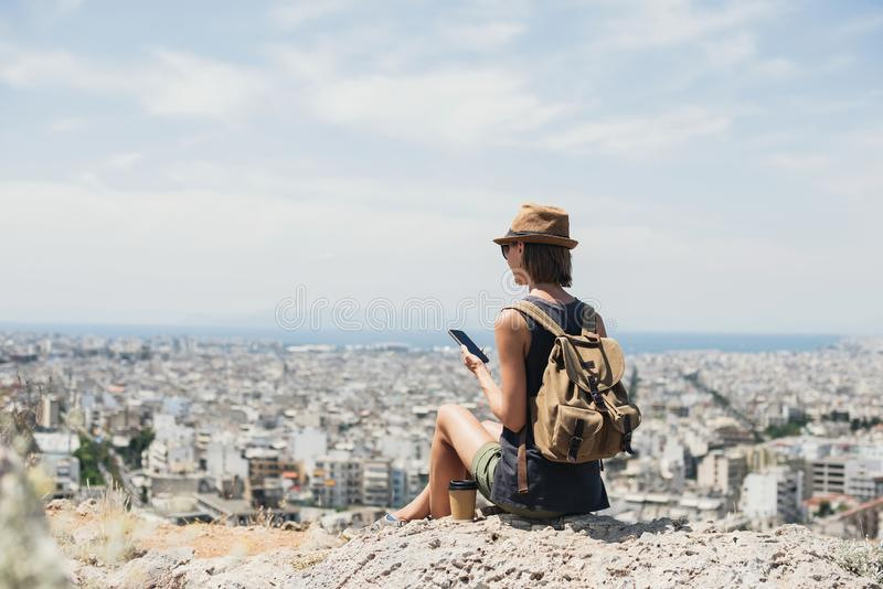 Young woman using smartphone during vacations. Girl holding mobile phone with a big city at background. Travel, lifestyle, tourist stock photography