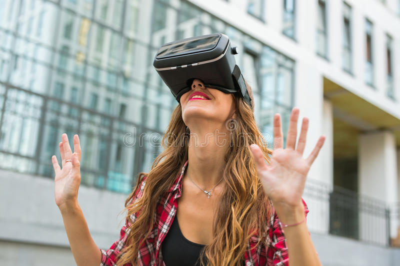 Young Beautiful Woman Using VR Outside. Young Beautiful Woman Using Virtual Reality Glasses Outside royalty free stock photography