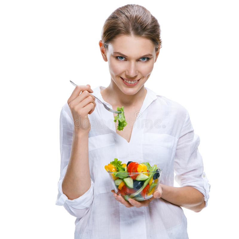 Young beautiful woman with vegetable salad bowl and fork in hand isolated on white background. Amusing girl of the european appearance eating with a fork royalty free stock photo
