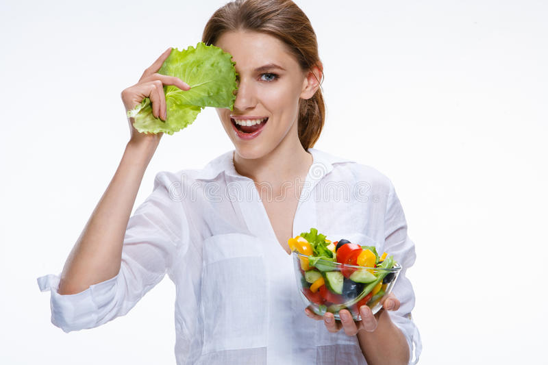 Young beautiful woman with vegetable salad bowl in one hand and cabbage leaf in other hand on white background. Comic girl of the european appearance closes an royalty free stock image