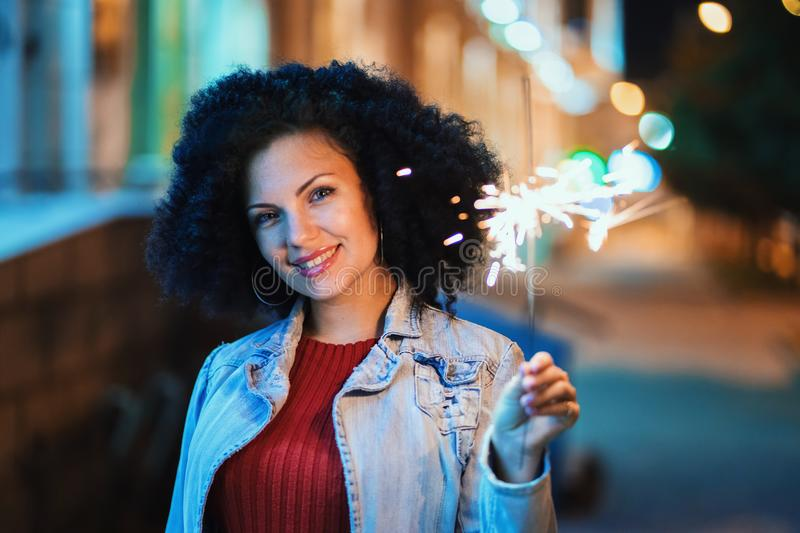 Young beautiful woman with very curly afro hair dancing with bengal fire at night illuminated street. Unusual trendy royalty free stock image