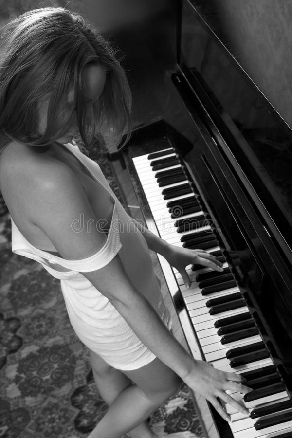 Download Young Beautiful Woman In A Vest Playing The Piano Stock Image - Image: 13074243