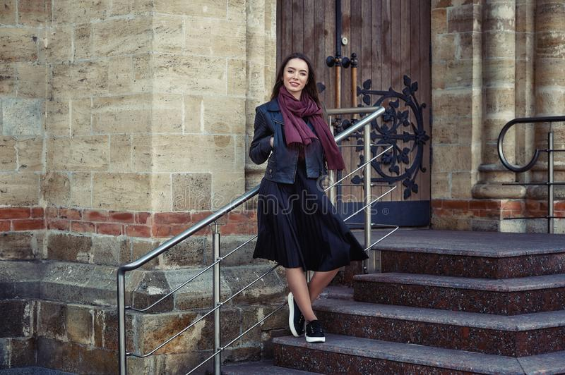 Young beautiful woman on a walk around the city . The girl wears a black jacket and skirt . royalty free stock photography