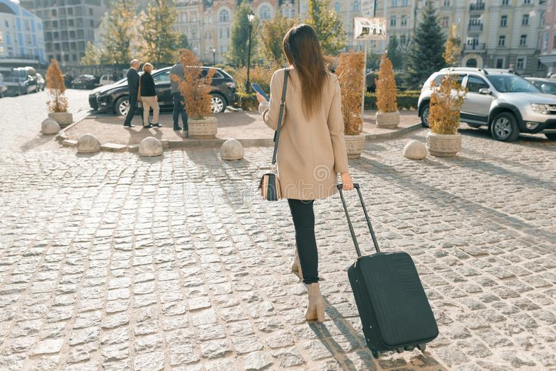 Young beautiful woman walking along city street with travel suitcase and cell phone. Fashionable brunette girl, view from the back royalty free stock photos