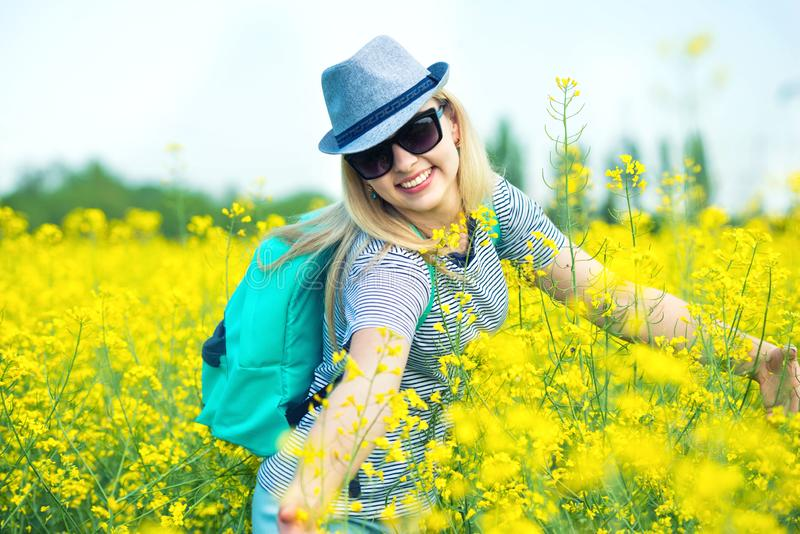 Young beautiful woman is walking along a flowering field on a sunny day. stock photography