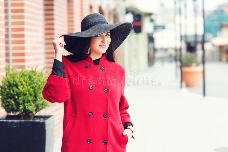 Young beautiful woman walking in city street. Female model with beauty makeup and hairstyle stock photo