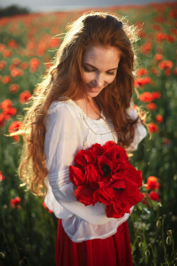 Young beautiful woman walking and dancing through a poppy field stock photography