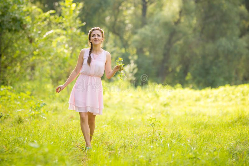 Young beautiful woman walking on green meadow with a bouquet of wildflowers in a light summer dress stock images