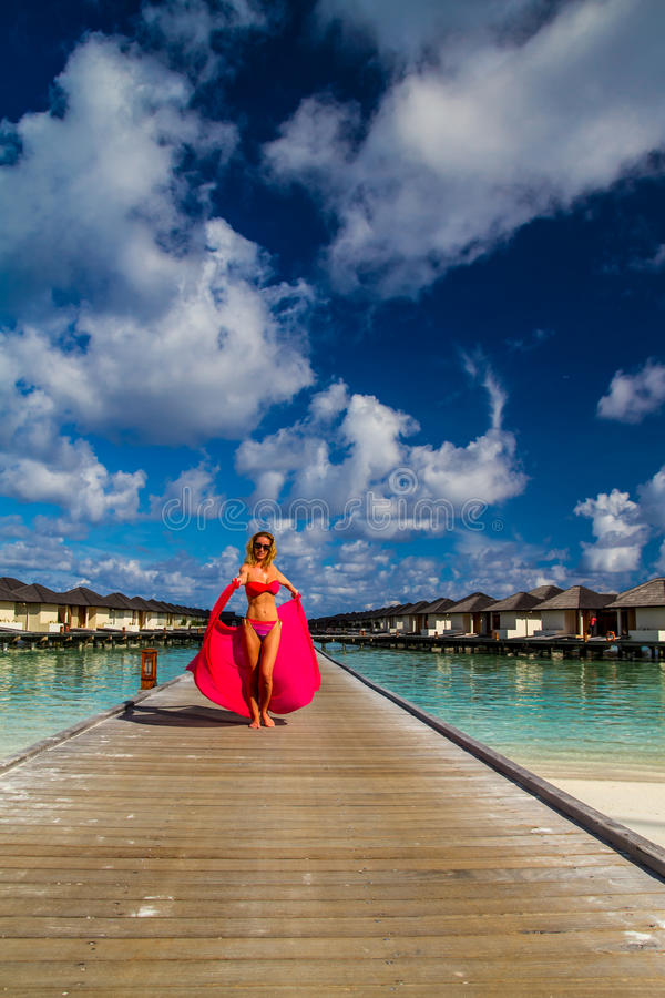 Young beautiful woman walking on a jetty, tropical vacation. Maldives beach with a young woman panorama. Luxury water villas, in exotic blue lagoon. Full screen stock photos