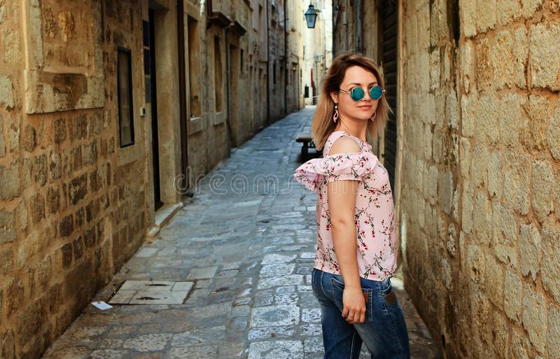 Young beautiful woman walking in old city street, summer Europe vacation, travel, fun, happy, smiling, sunglasses. stock photos
