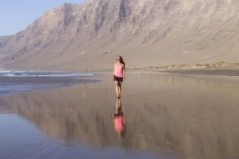 Young beautiful woman walking by the seashore in Lanzarote, Canary islands. Summer. reflection in the water. lifestyle stock image