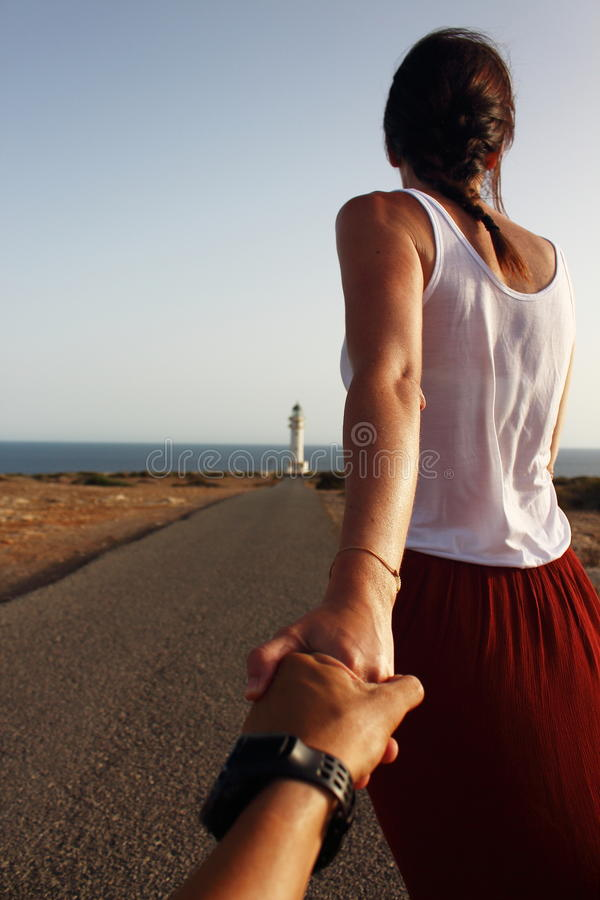 Young beautiful woman walking slowly to Cap de Barberia's lighthouse during an amazing summer sunset.  royalty free stock image