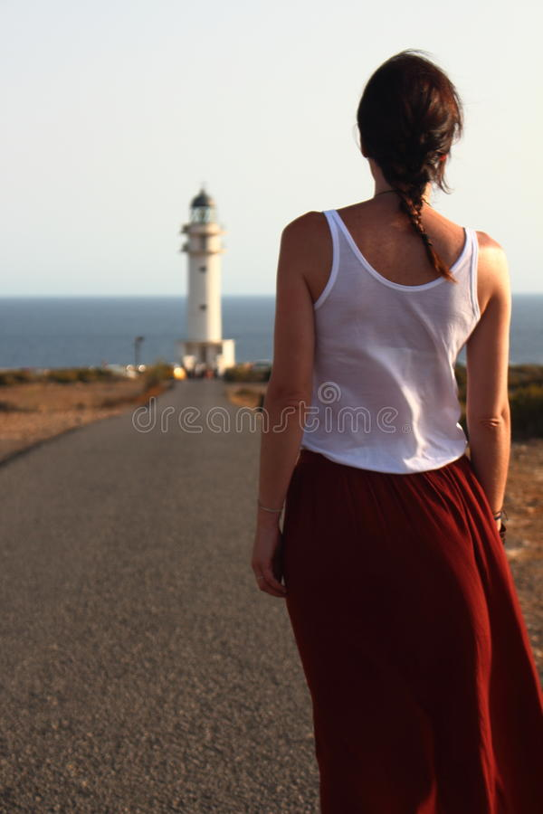 Young beautiful woman walking slowly to Cap de Barberia's lighthouse during an amazing summer sunset.  royalty free stock images
