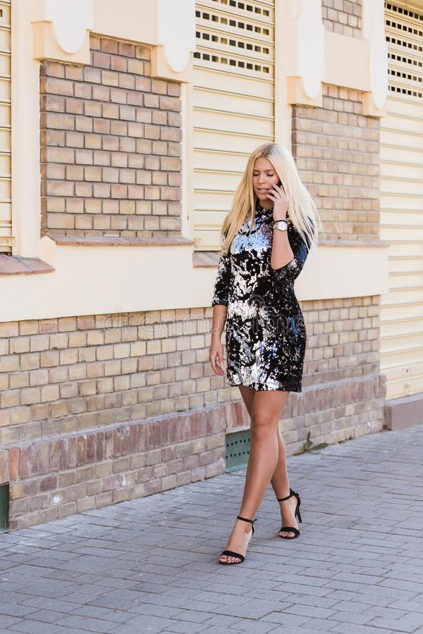 Young beautiful woman walking on the street and talking on the mobile phone. Portrait of a beautiful young attractive woman  in a black dress walking on the stock photos