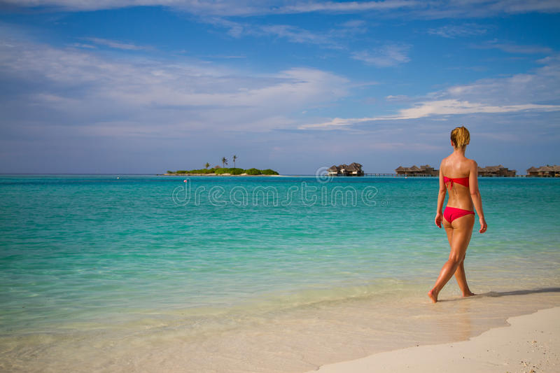 Young beautiful woman walking on a tropical beach. Maldives beach with a young woman panorama. Luxury water villas, in exotic blue lagoon. Full screen screen royalty free stock photos