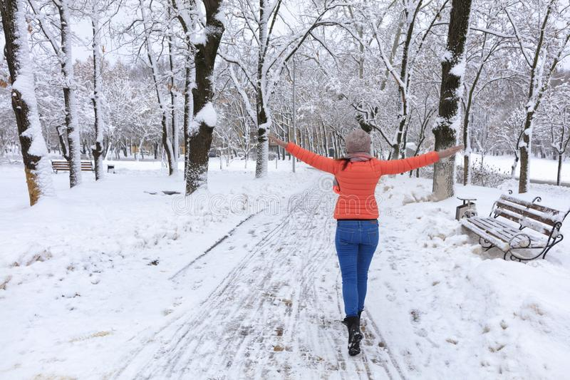 A young beautiful woman walks in winter along an alley in a snowy fabulous city park with her arms spread like wings stock image