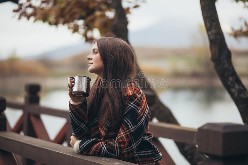 Young beautiful woman in a warm classic coat drinking tea near lake. Autumn atmosphere royalty free stock photography