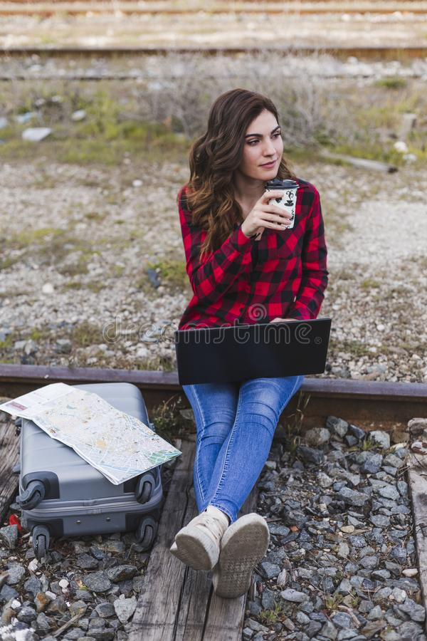 Young beautiful woman wearing casual clothes, sitting on the railway with suitcase, laptop and a map, she is smiling and holding a. Cup of coffee. Outdoors royalty free stock photo