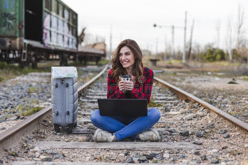 Young beautiful woman wearing casual clothes, sitting on the railway with suitcase, laptop and a map, she is smiling and holding a. Cup of coffee. Outdoors stock photography