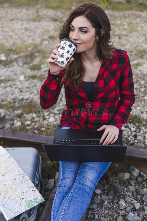 Young beautiful woman wearing casual clothes, sitting on the railway with suitcase, laptop and a map, she is smiling and holding a. Cup of coffee. Outdoors royalty free stock image