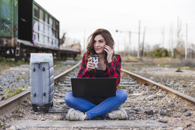 Young beautiful woman wearing casual clothes, sitting on the railway with suitcase, laptop and talking on her mobile phone., she. Is smiling and holding a cup stock images