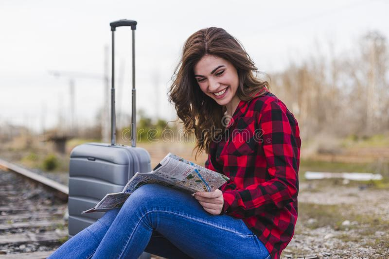 Young beautiful woman wearing casual clothes, sitting on the railway with suitcase and a map, she is smiling. Outdoors lifestyle. Travel concept, city, fashion stock photography