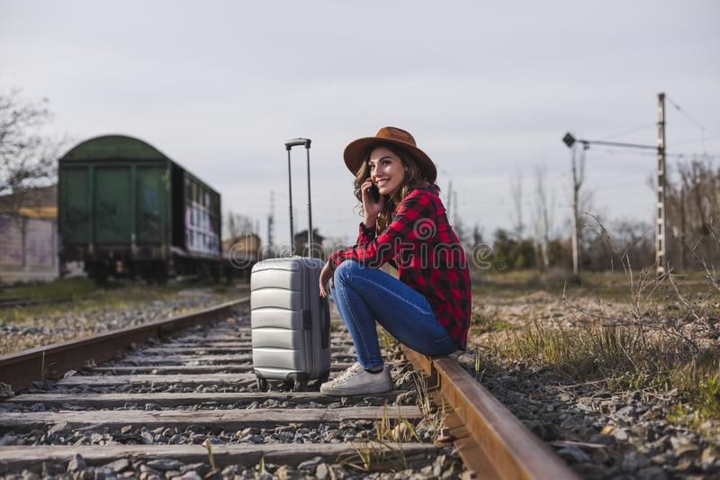 Young beautiful woman wearing casual clothes, sitting on the railway with suitcase and mobile phone and smiling. Outdoors. Lifestyle. Travel concept stock photo