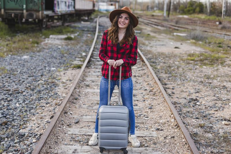 Young beautiful woman wearing casual clothes, walking by the railway with suitcase and a bag. She is smiling. Outdoors lifestyle. Travel concept royalty free stock photos