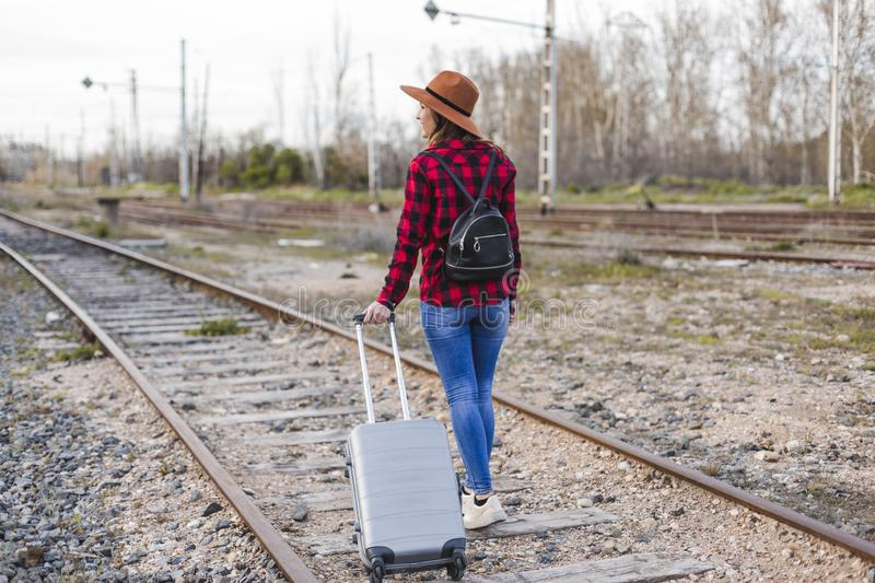 Young beautiful woman wearing casual clothes, walking by the railway with suitcase and a bag. She is smiling. Outdoors lifestyle. Travel concept stock photography