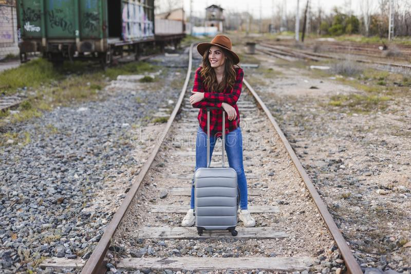 Young beautiful woman wearing casual clothes, walking by the railway with suitcase and a bag. She is smiling. Outdoors lifestyle. Travel concept stock images