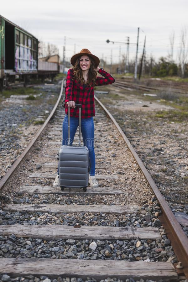 Young beautiful woman wearing casual clothes, walking by the railway with suitcase and a bag. She is smiling. Outdoors lifestyle. Travel concept royalty free stock photo