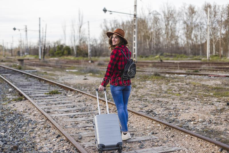 Young beautiful woman wearing casual clothes, walking by the railway with suitcase and a bag. She is smiling. Outdoors lifestyle. Travel concept royalty free stock image