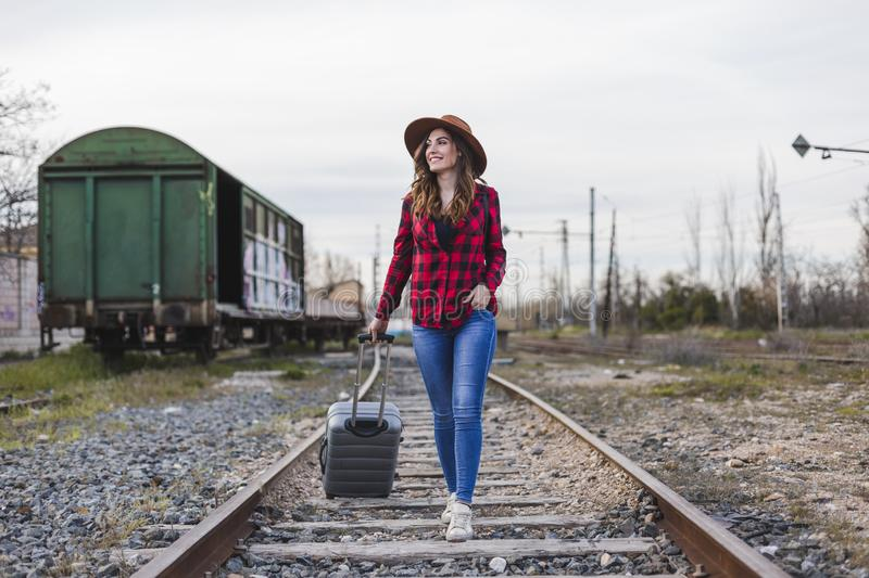 Young beautiful woman wearing casual clothes, walking by the railway with suitcase and a bag. She is smiling. Outdoors lifestyle. Travel concept stock image