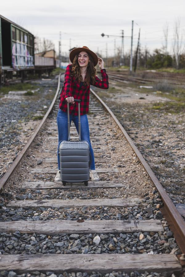 Young beautiful woman wearing casual clothes, walking by the railway with suitcase and a bag. She is smiling. Outdoors lifestyle. Travel concept royalty free stock images