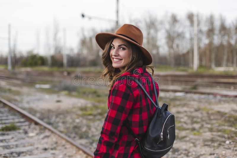 Young beautiful woman wearing casual clothes, walking by the railway with suitcase and a bag. She is smiling. Outdoors lifestyle. Travel concept royalty free stock photography