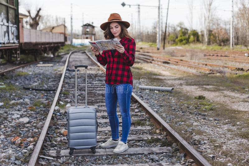 Young beautiful woman wearing casual clothes, walking by the railway with suitcase and a map, she is smiling. Outdoors lifestyle. Travel concept royalty free stock images
