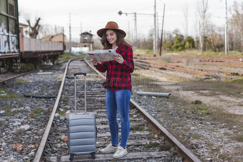 Young beautiful woman wearing casual clothes, walking by the railway with suitcase and a map, she is smiling. Outdoors lifestyle. Travel concept royalty free stock photo