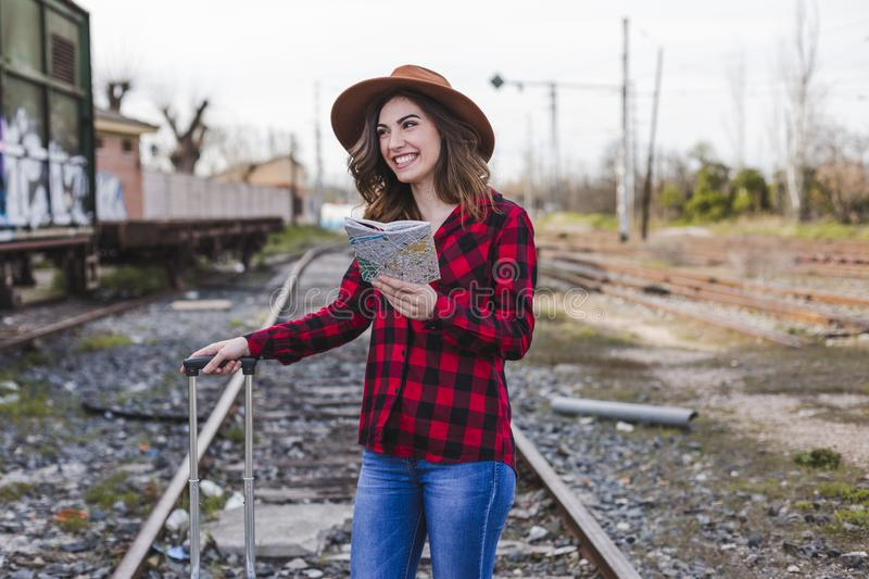 Young beautiful woman wearing casual clothes, walking by the railway with suitcase and a map, she is smiling. Outdoors lifestyle. Travel concept stock image
