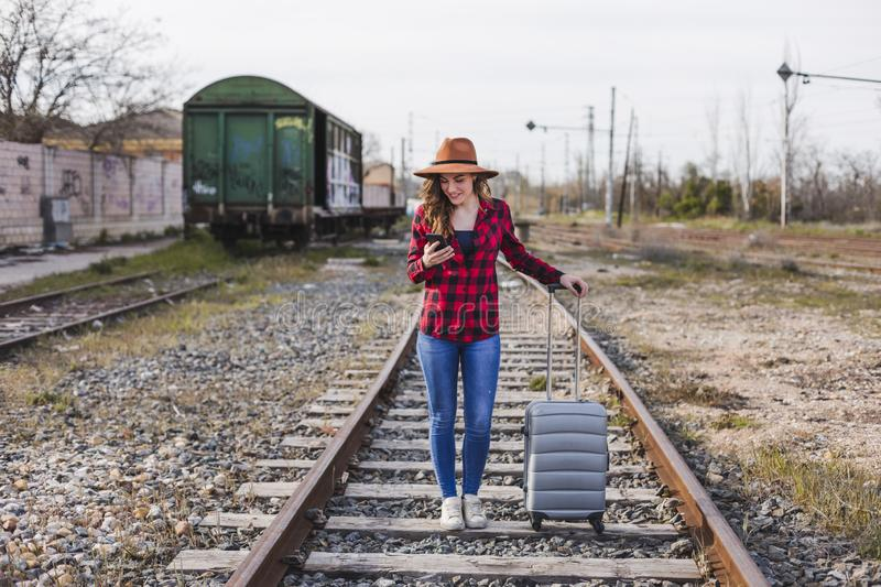 Young beautiful woman wearing casual clothes, walking by the railway with suitcase and mobile phone and smiling. Outdoors. Lifestyle. Travel concept, city royalty free stock image