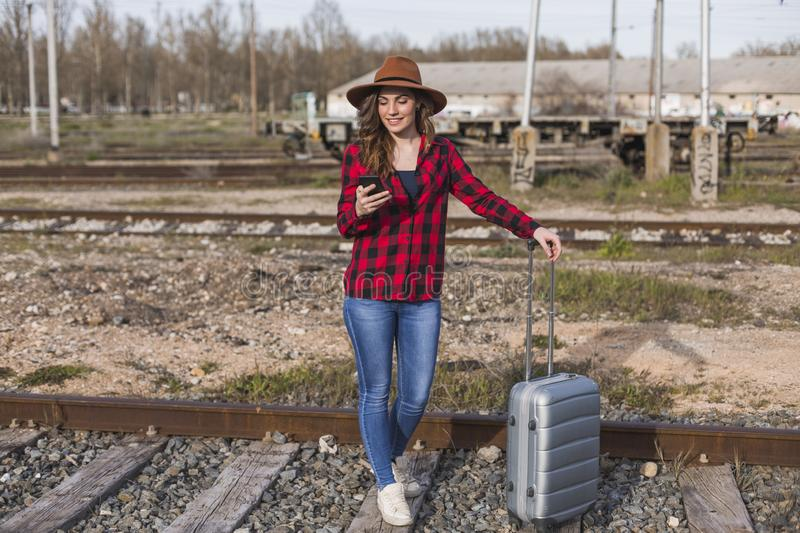 Young beautiful woman wearing casual clothes, walking by the railway with suitcase and mobile phone and smiling. Outdoors. Lifestyle. Travel concept, city stock image