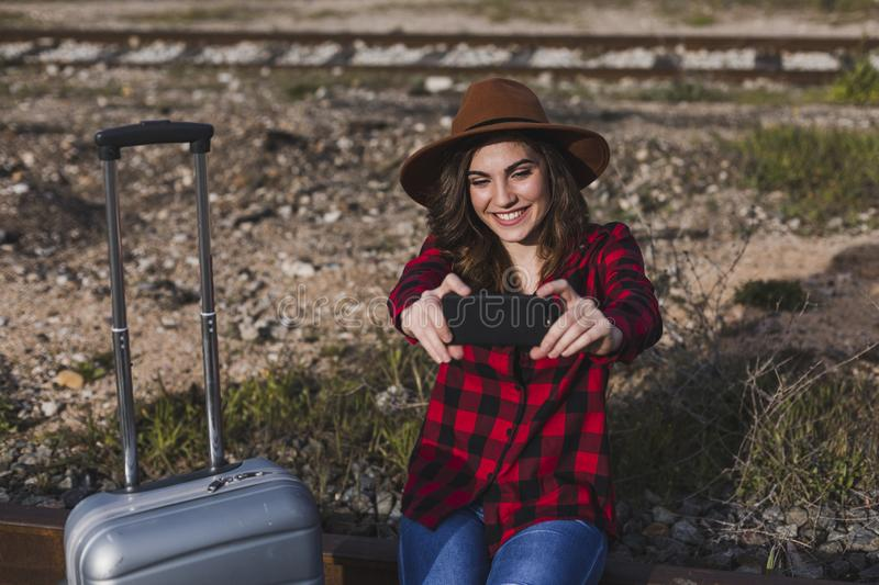 Young beautiful woman wearing casual clothes, walking by the railway with suitcase and mobile phone and smiling. Outdoors. Lifestyle. Travel concept. She is stock photography