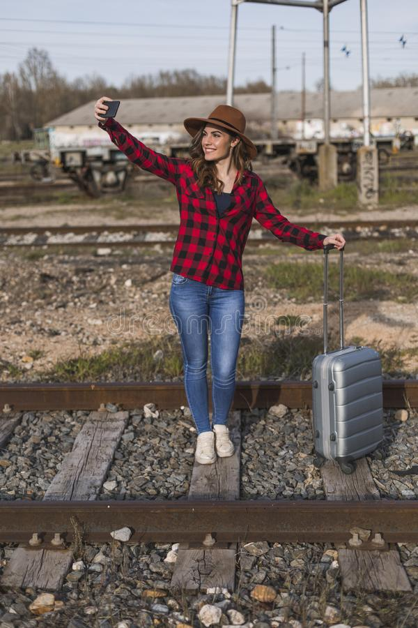 Young beautiful woman wearing casual clothes, walking by the railway with suitcase and mobile phone and smiling. Outdoors. Lifestyle. Travel concept. She is royalty free stock images