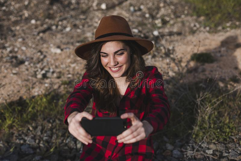 Young beautiful woman wearing casual clothes, walking by the railway with suitcase and mobile phone and smiling. Outdoors. Lifestyle. Travel concept. She is stock photos
