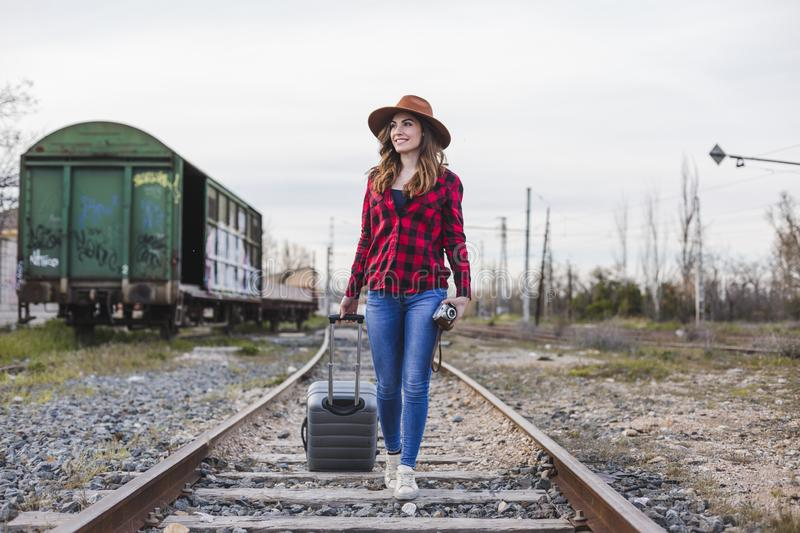 Young beautiful woman wearing casual clothes, walking by the railway with suitcase and a vintage camera. She is smiling. Outdoors. Lifestyle. Travel concept royalty free stock photos