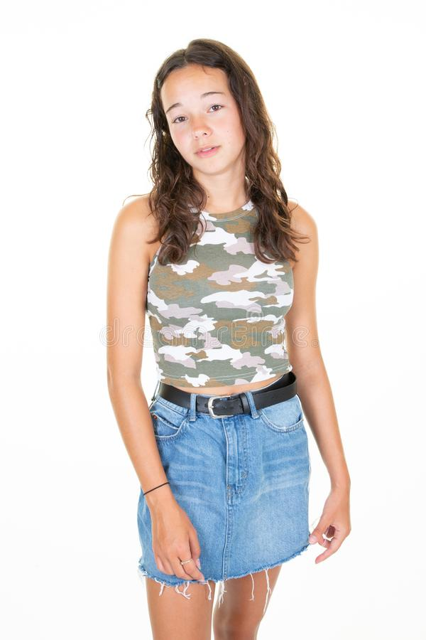 Young beautiful woman wearing denim skirt camouflage t shirt over isolated white background. A Young beautiful woman wearing denim skirt camouflage t shirt over royalty free stock images
