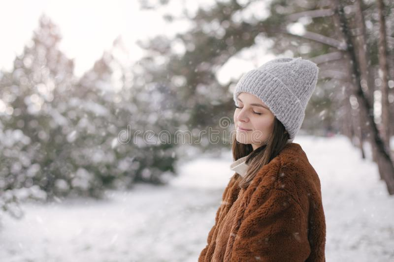 Woman in faux fur coat and woolen hat enjoying snowfall. Young beautiful woman wearing fashionable faux fur coat and woolen hat enjoying snowfall in a winter royalty free stock images
