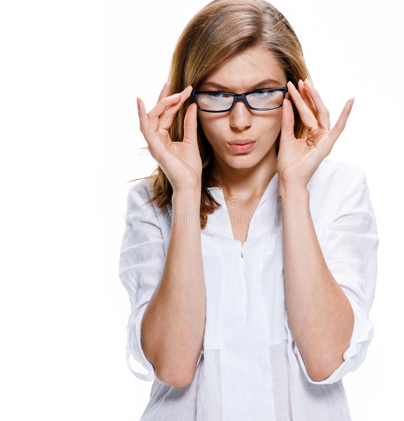Young beautiful woman wearing glasses isolated on white background. Incredulous girl of european appearance in a white shirt looking through the glasses stock image