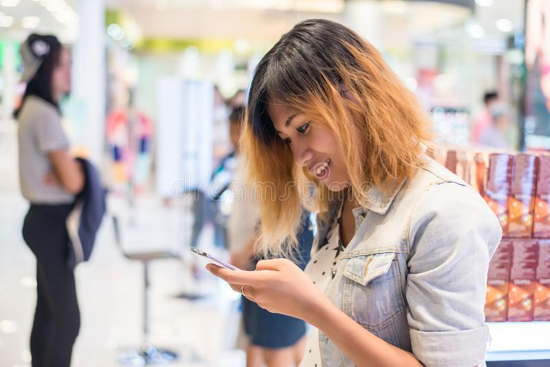 young beautiful woman wearing jean jacket texting on the smartphone walking in the shopping mall. royalty free stock images