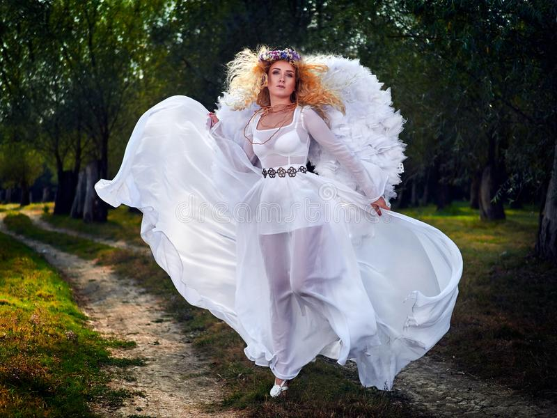 Young woman wearing long white dress and angel wings royalty free stock images